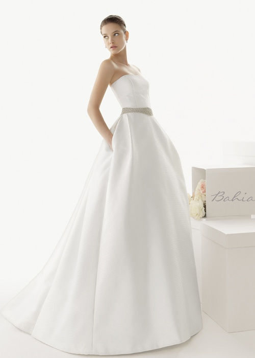 a plain minimalist strapless wedding ballgown with an embellished sash and pockets for a wow look