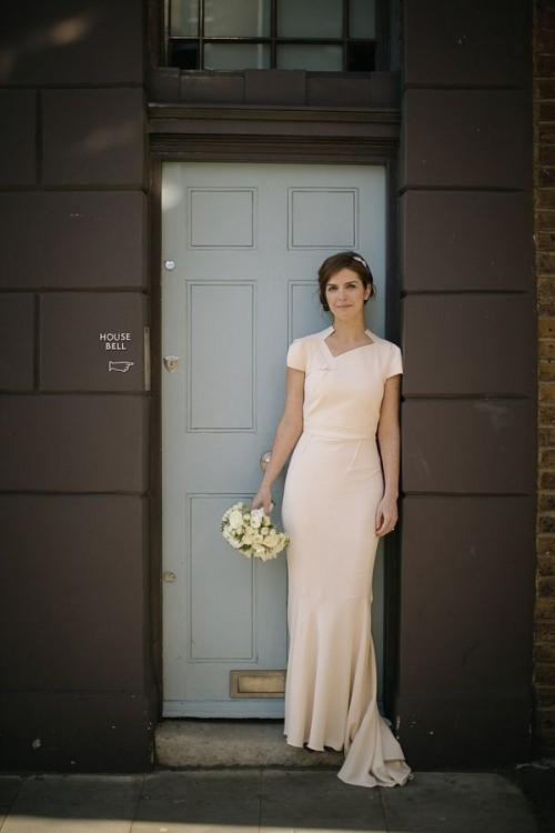 a blush minimalist sheath wedding dress with a geometric neckline, short sleeves and a train is romantic