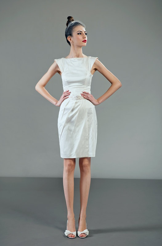 a minimalist knee wedding dress with a plain bodice and a pleated skirt, cap sleeves for a modern and fresh look