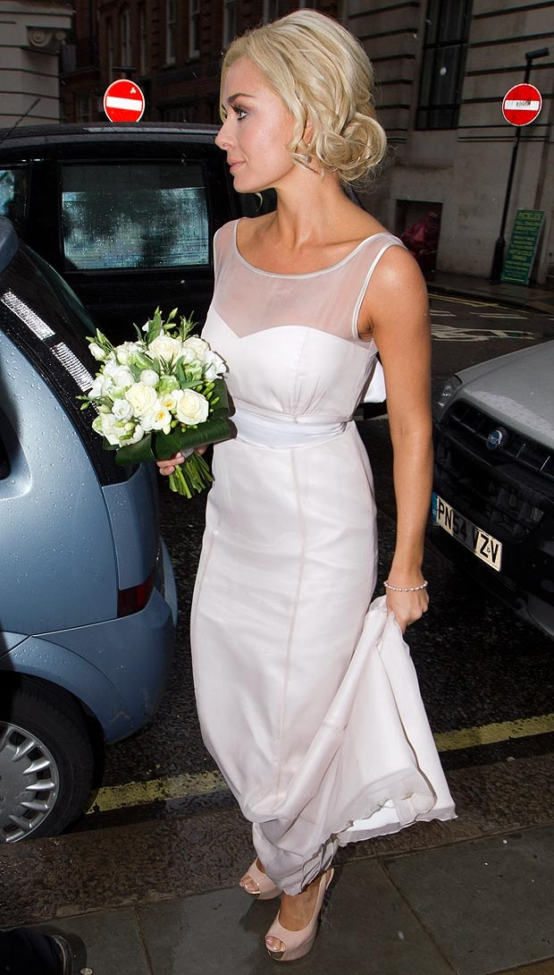 a minimal wedding dress with no sleeves and an illusion neckline plus a sash for a chic modern look
