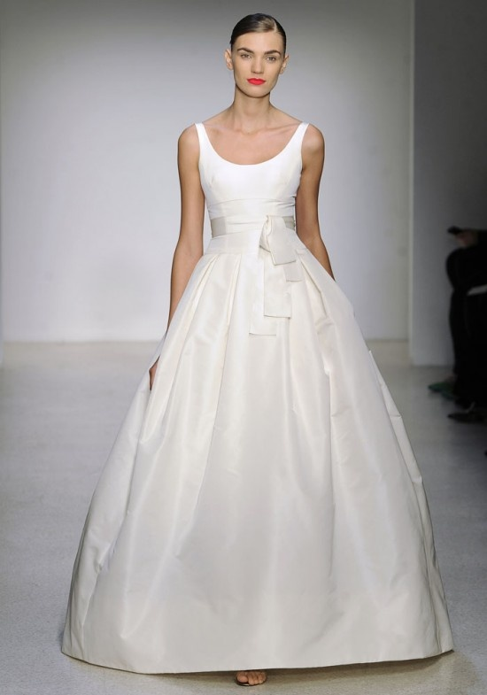 a minimalist wedding ballgown with no sleeves, a scoop neckline and a draped full skirt plus a sash