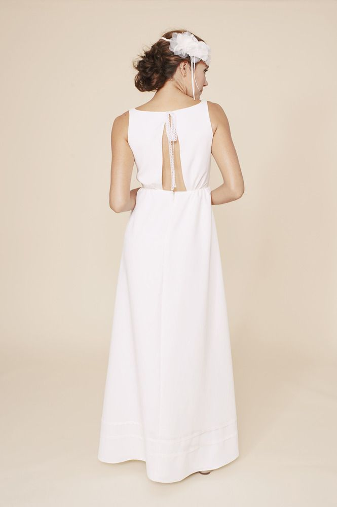 a minimalist A line wedding dress with a cutout back and some beading hanging in the cutout is a cool idea for a minimal to retro look