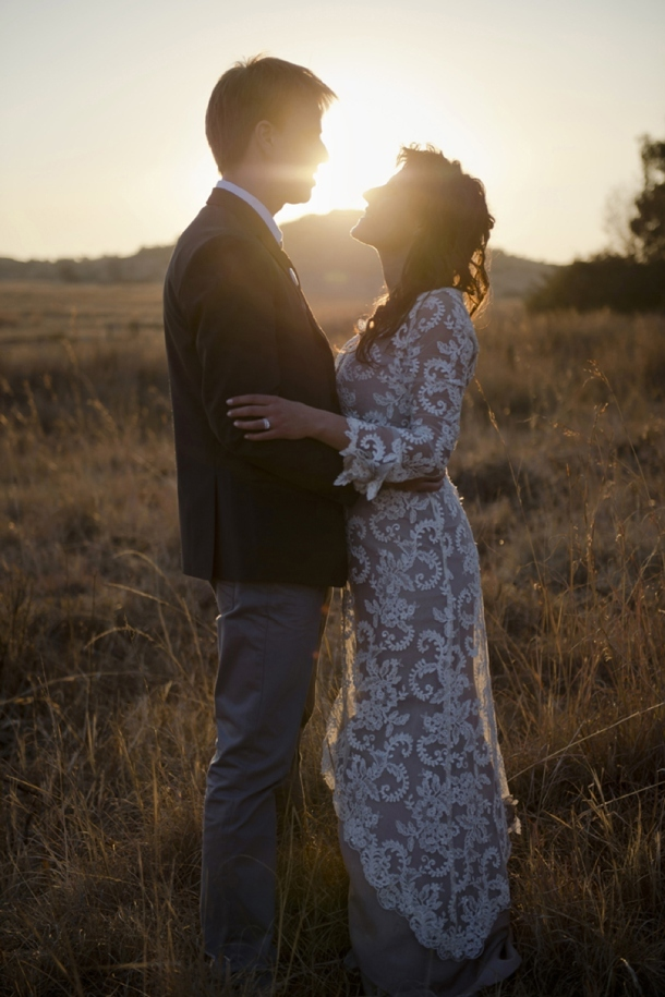 a fitting nude lace wedding dress with short sleeves and a high neckline for a casual sunset wedding ceremony