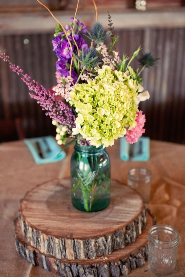 a bright barn wedding centerpiece of a jar with bright purple and yellow blooms placed on wood slices