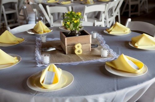 a box with greenery and yellow blooms is a nice and cute barn wedding centerpiece