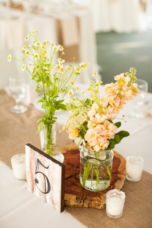 a wood slice with neutral and pastel blooms plus some greenery and a table number for a cute and cozy barn wedding centerpiece