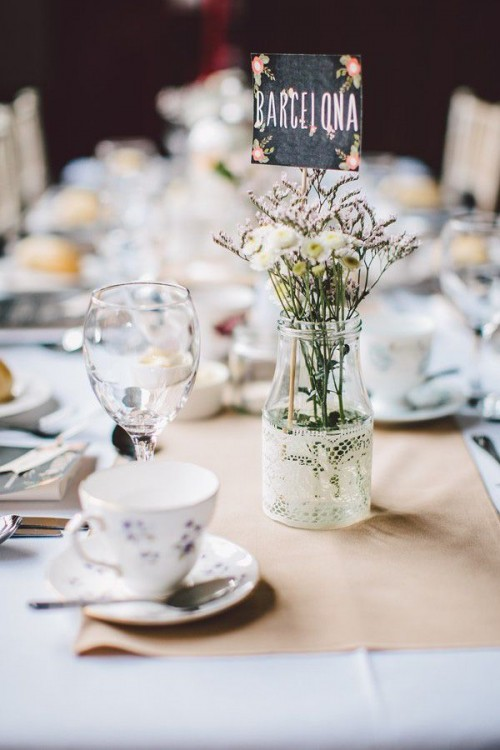 a clear vase wrapped with white lace, with dried herbs and flowers plus a table name