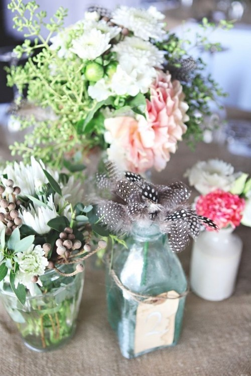 bright and neutral blooms, greenery, feathers all palced into clear glass vases is a lush and chic barn centerpiece