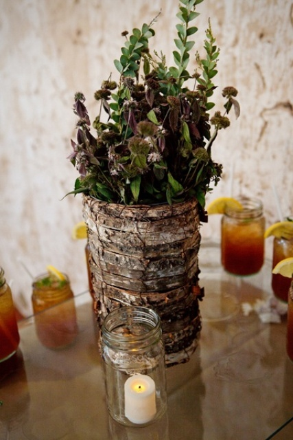 a bark wrapped vase with greenery and dark foliage is a cozy rustic wedding centerpiece