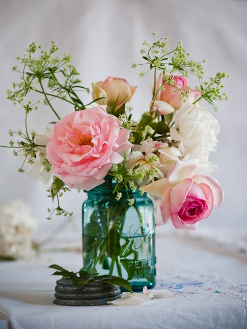a blue jar with pink and neutral blooms plus greenery will be nice for a rustic or barn wedding