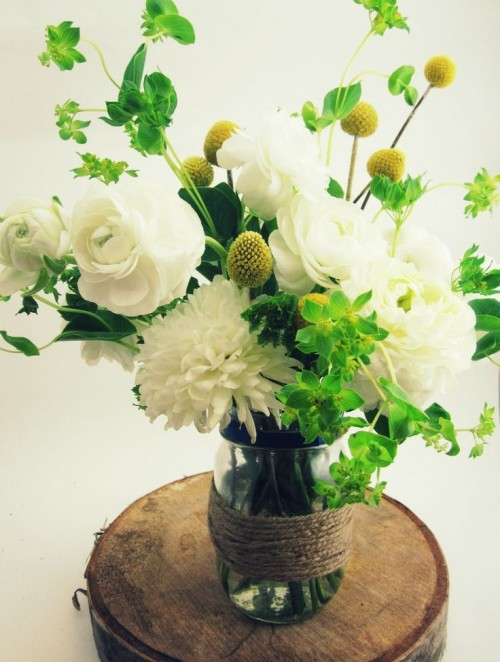 a wood slice with a jar wrapped with yarn, white blooms and greenery plus billy balls is a cool decoration