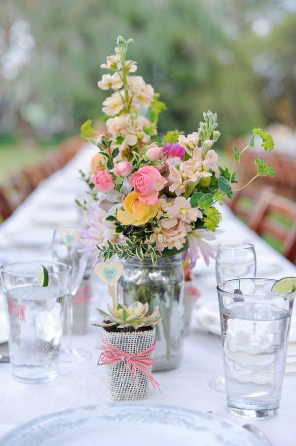 a neutral barn wedding centerpiece of pastel and yellow blooms, greenery and a succulent in a pot