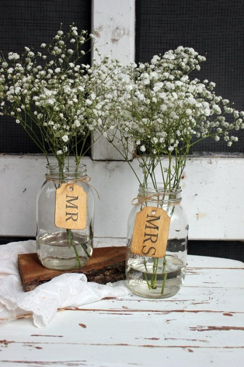 clear jars with baby's breath and tags are cool and simple barn wedding centerpieces