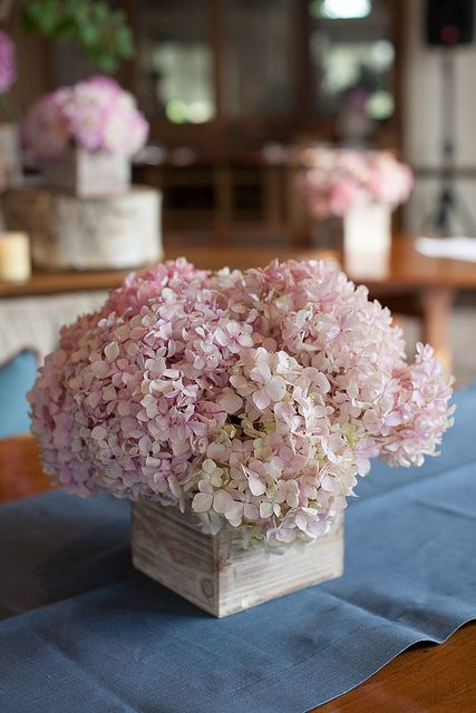 a wooden box with soft pink flowers is a cute rustic or barn wedding centerpiece