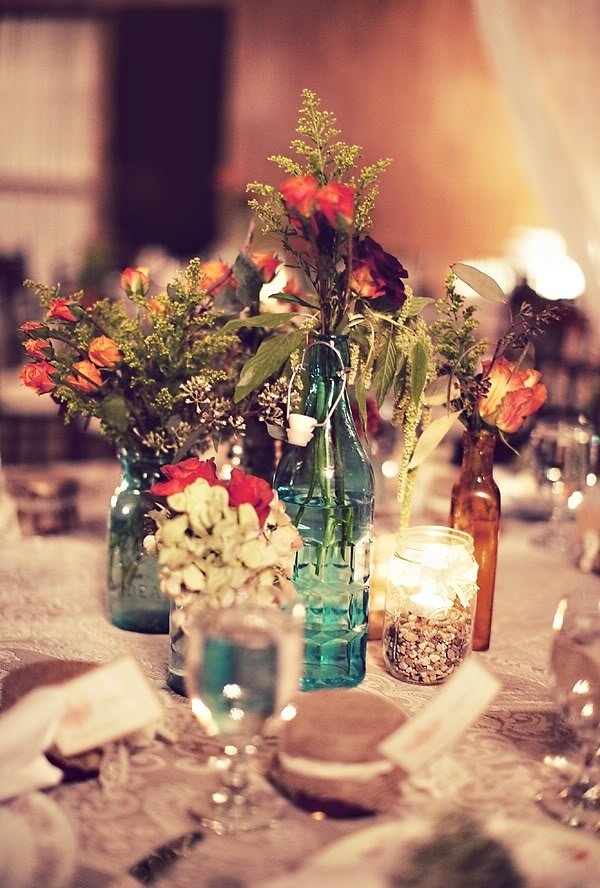 bottles and vases with simple greenery and bright and white blooms plus candles is a combo that works for many weddings including barn ones