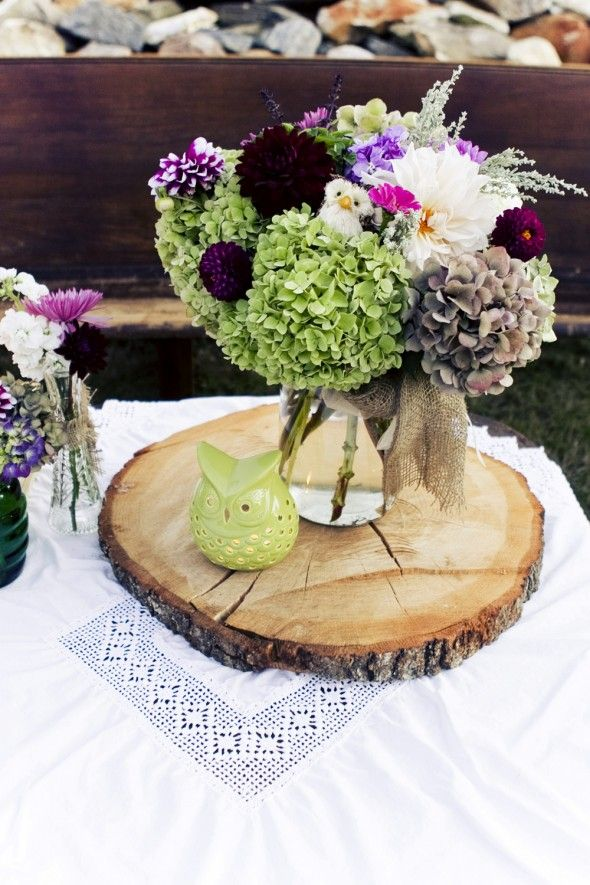a wood slice with a green owl candleholder and a jar with bright and bold blooms