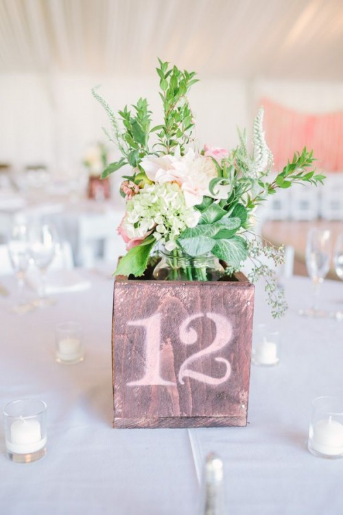 a plywood box with a table number and pastel blooms and greenery is a cool barn wedding centerpiece idea
