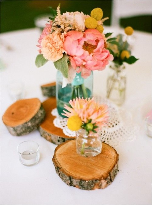 a bright wedding centerpiece of wood slices, a doily and pastel blooms in jars