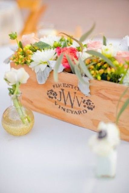 a plywood box with bright and white blooms and greenery is a stylish barn wedding centerpiece idea