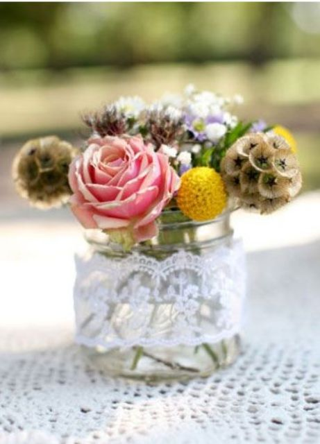 a jar wrapped with lace with pink and yellow blooms and darker ones for a rustic or barn wedding
