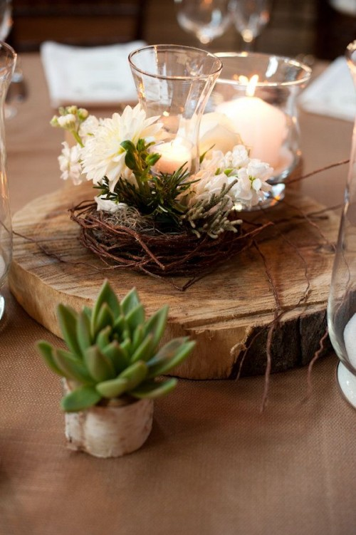 a wood slice with a succulent, a nest with white blooms and white candles is a nice centerpiece for a barn wedding