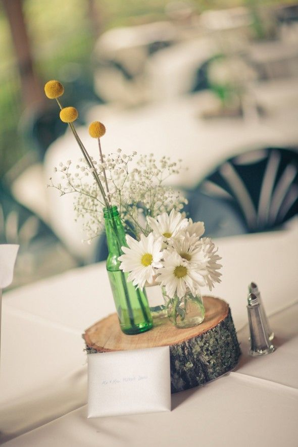 a wood slice with white blooms and billy balls plus a table name is a stylish idea for a wedding centerpiece