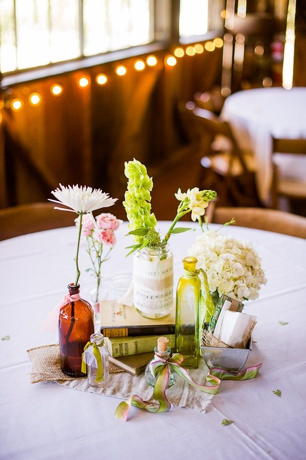 a barn wedding centerpiece with bottles and jars, white, pink and green blooms, a stack of books and some fabric