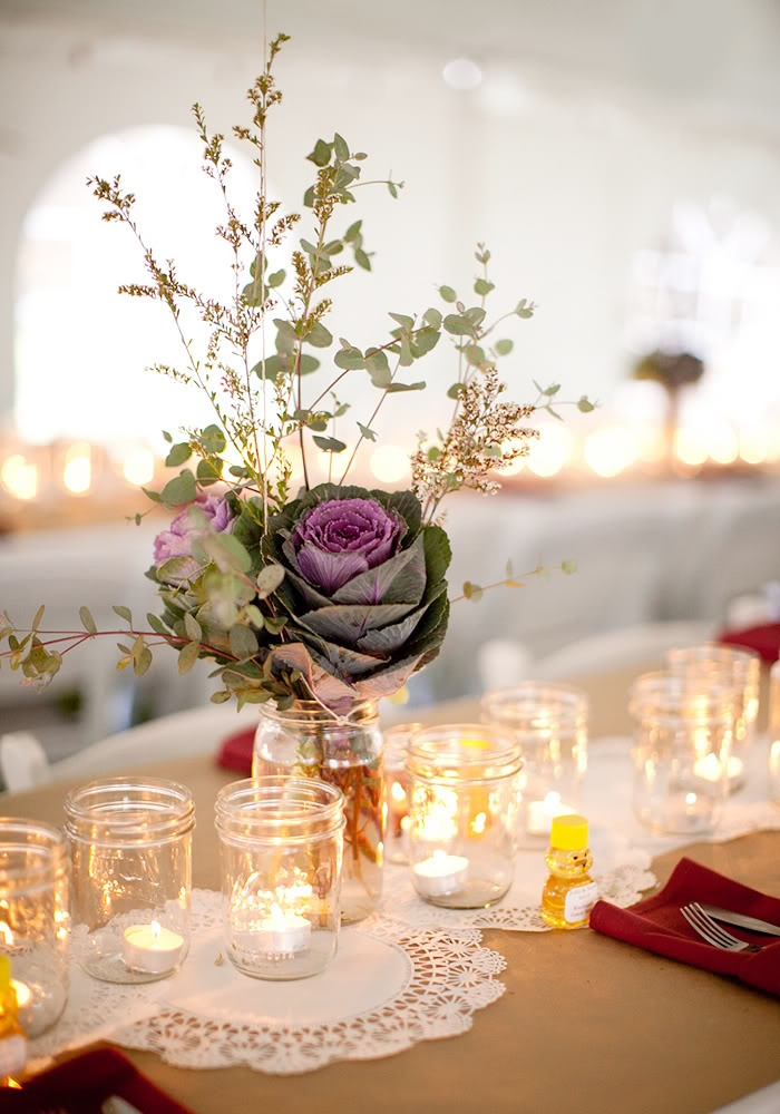 a barn wedding centerpeice of a jar with greenery, blooms and cabbages plus candles around looks very rustic