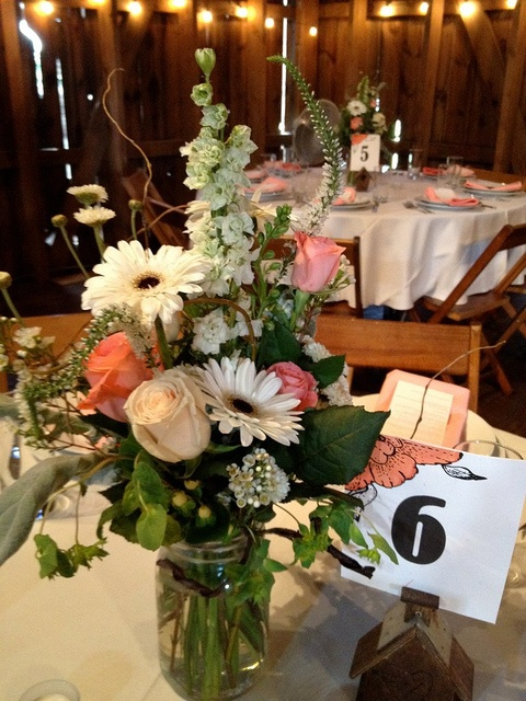 a lush floral wedding centerpiece of white and pink blooms, greenery and foliage and a table number
