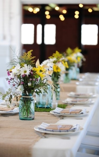 a brigth barn wedding centerpiece of white, pink and yellow blooms and greenery for a rustic wedding