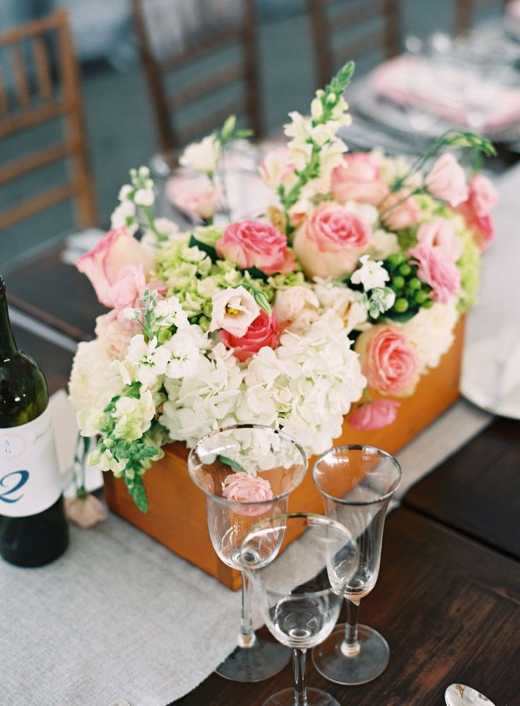 a plywood box with white and pink blooms and greenery plus some berries is a chic barn wedding centerpiece