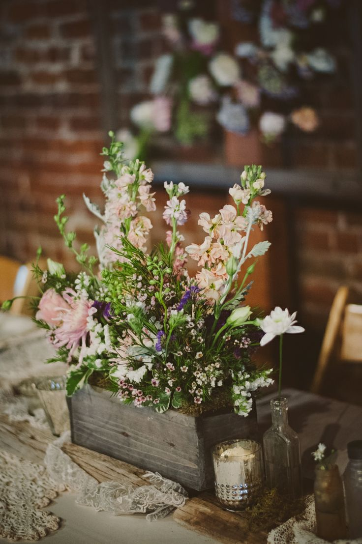 a cozy barn wedding centerpiece of a wooden box and some neutral and pink flowers plus greenery
