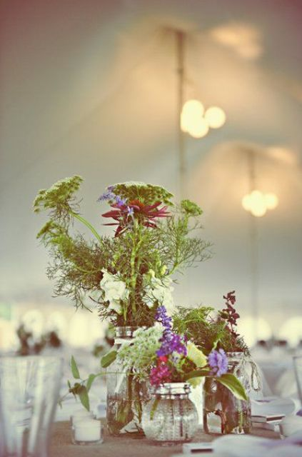 simple jars and vases with green and pink blooms plus candles for a barn wedding centerpiece