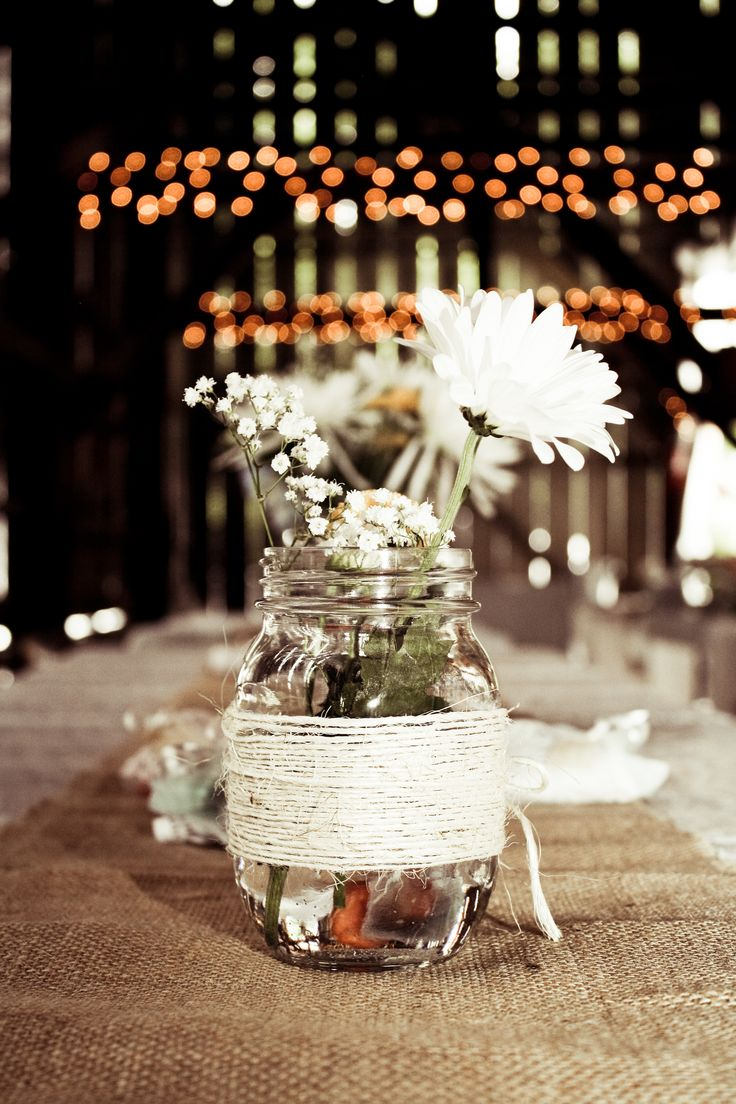 a jar wrapped with yarn and white blooms is a nice centerpiece for a cool barn wedding