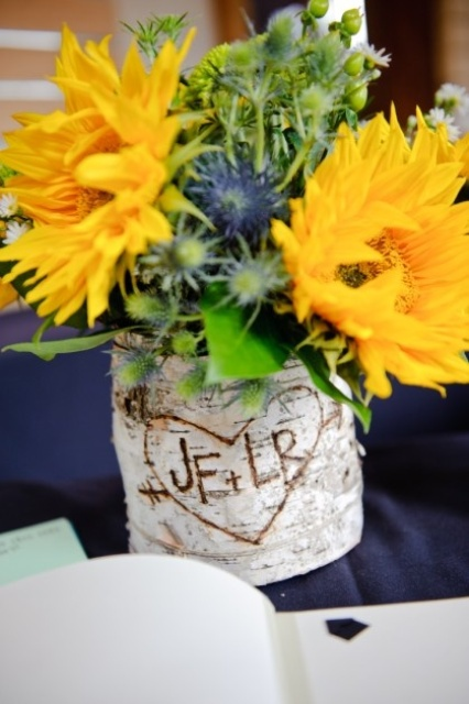 a vase wrapped with cutout bark and yellow blooms and thistles for a bright and cheerful wedding centerpiece