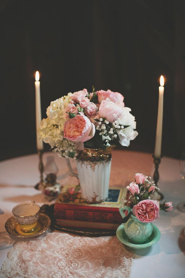 an elegant wedding centerpiece of a vintage vase with copper and white and pink blooms and candles