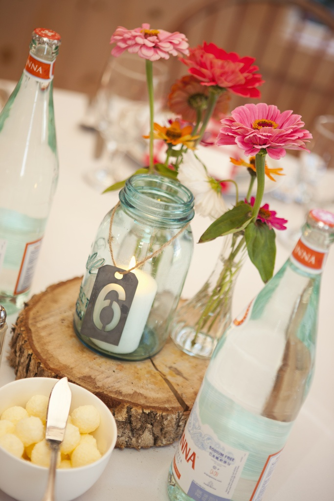 a candle in a har with a tag, a wood slice and some bright pink blooms for a barn wedding centerpiece