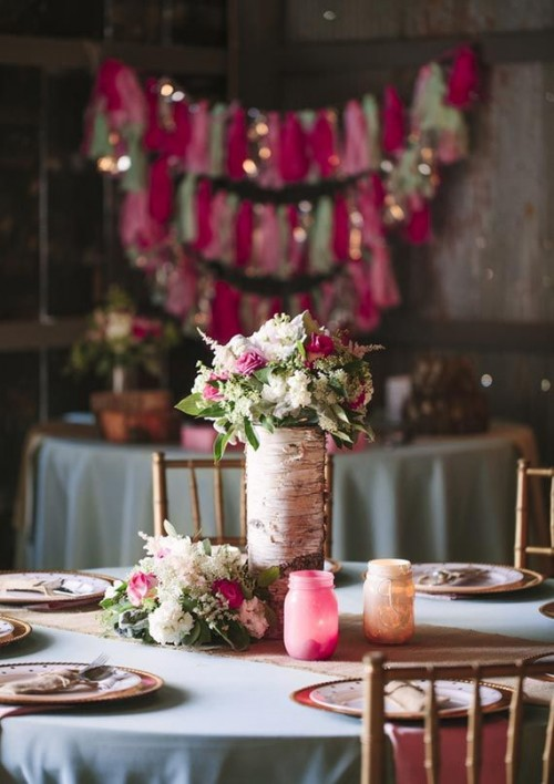 a rustic wedding centerpiece of white and pink blooms with greenery in a vase wrapped with bark