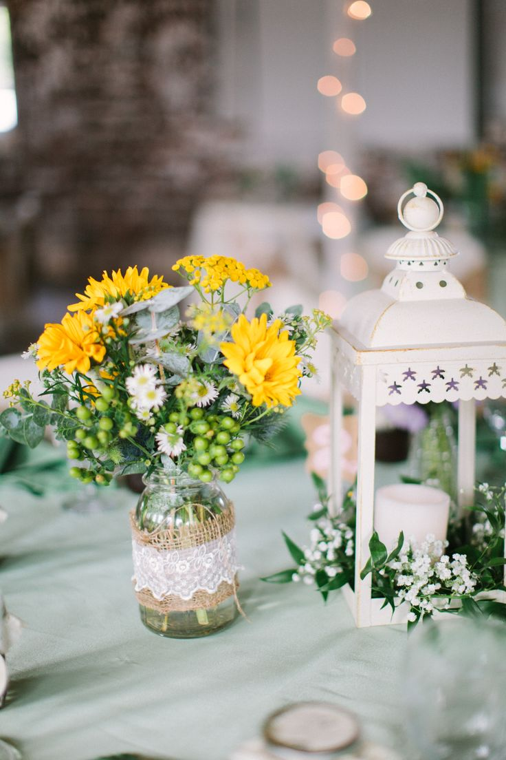 a jar wrapped with burlap and lace and white and yellow blooms, a white candle lantern with greenery and white flowers