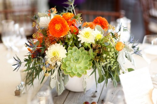 a barn wedding centerpiece of neutral, orange and green blooms, greenery and thistles is super lush