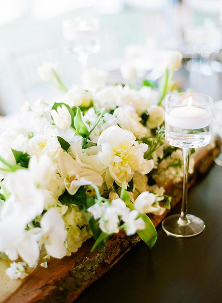 white blooms and greenery placed into a piece of wood is a simple and stylish barn wedding centerpiece