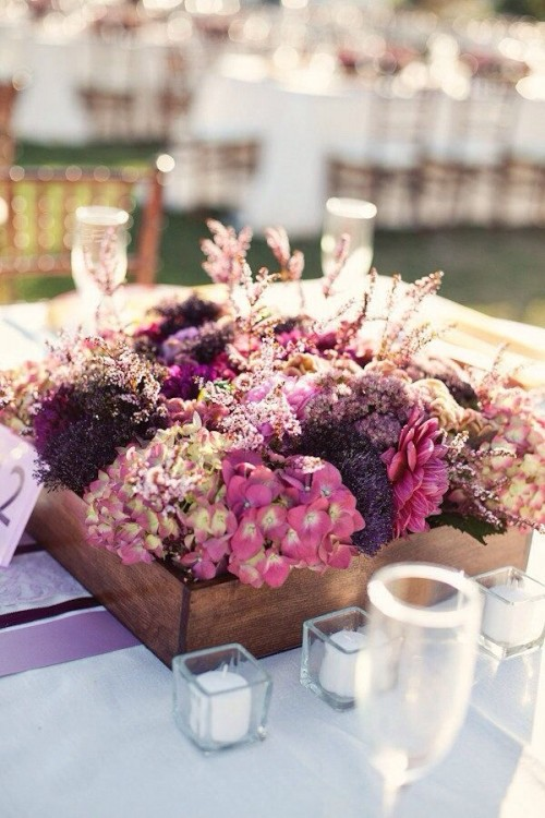 a bright fall wedding centerpiece of pink and purple blooms and herbs is a stylish idea for a barn wedding