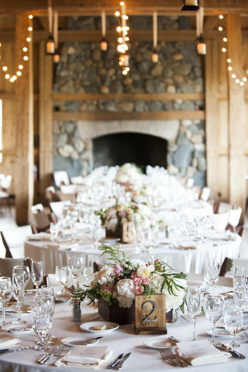 a wooden box with pink and white flowers plus some greenery is a chic and cozy barn wedding centerpiece