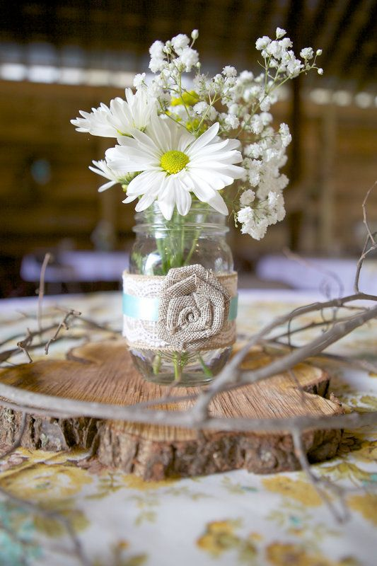 a wood slice with a jar with a fabric bloom and some white blooms in it for a cute barn wedding centerpiece