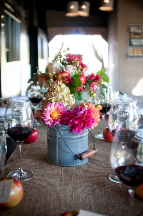 a galvanized bucket with bright blooms and greenery is a cool rustic option to go for