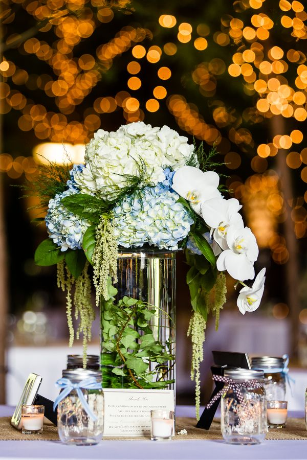 a clear glass vase with greenery and white and blue blooms plus white orchids for a quirky look