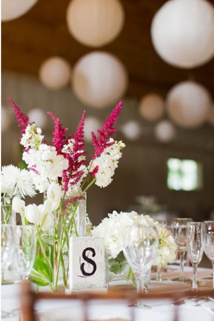white and fuchsia blooms and greenery in clear vases are simple and cute barn wedding centerpieces