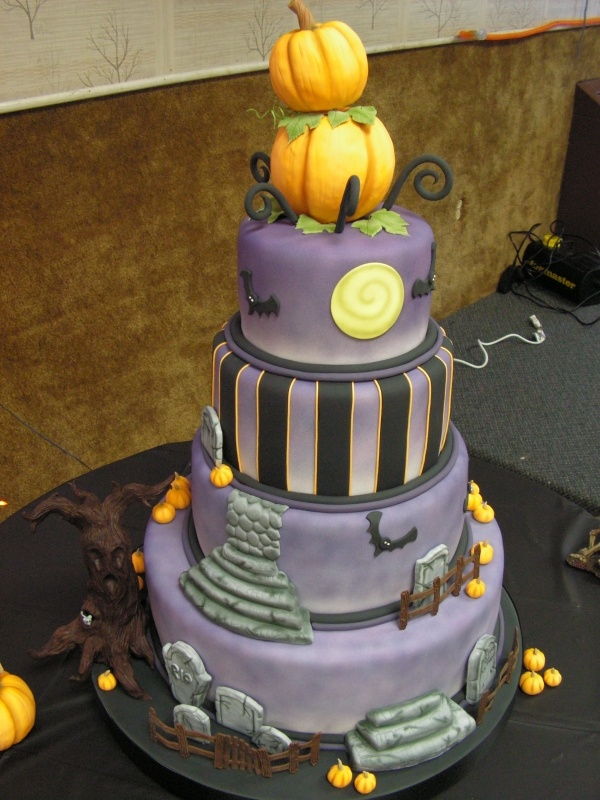 a creative purple wedding cake with a striped tier and graveyard and bat ones, with a scary tree and stacked pumpkins on top for a Halloween wedding
