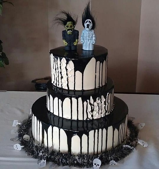a round white wedding cake with black dripping and scary toppers on top looks spooky and very statement like