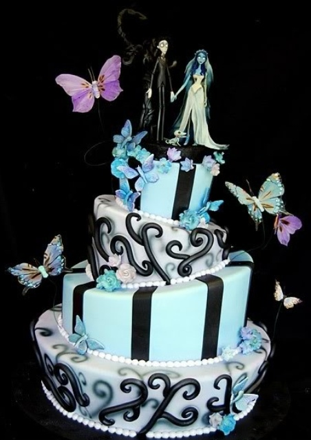 a whimsical blue, white and black wedding cake with stripes and patterns, blue flowers and butterflies and Nightmare Before Christmas toppers